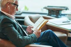 Leitura contemporânea do homem superior no café imagem de stock