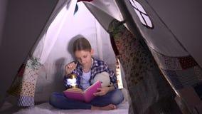 Leitura da criança, criança que estuda na noite, menina que joga na sala de jogos, aprendendo na barraca video estoque