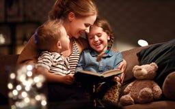 Leitura da fam?lia da noite a m?e l? crian?as livro antes de ir para a cama imagem de stock