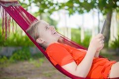 Leitura da jovem mulher no leitor eletrônico da tabuleta que relaxa no hamm Fotos de Stock Royalty Free