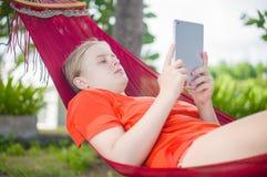 Leitura da jovem mulher no leitor eletrônico da tabuleta que relaxa no hamm Foto de Stock Royalty Free