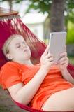 Leitura da jovem mulher no leitor eletrônico da tabuleta que relaxa no hamm Fotografia de Stock