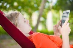 Leitura da jovem mulher no leitor eletrônico da tabuleta que relaxa no hamm Imagens de Stock