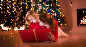 Leitura da mãe e da filha no lugar do fogo na Noite de Natal Imagem de Stock Royalty Free