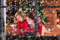 Leitura da mãe e da filha no lugar do fogo na Noite de Natal Fotografia de Stock Royalty Free