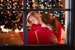 Leitura da mãe e da filha no lugar do fogo na Noite de Natal Foto de Stock Royalty Free