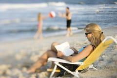 Leitura da mamã na cadeira de sala de estar na praia.
