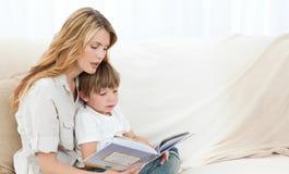 Leitura da matriz com seu filho Imagens de Stock