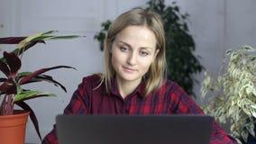 Leitura da menina ao sentar-se em um portátil em sua sala video estoque