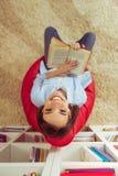 Leitura da menina em casa Imagens de Stock