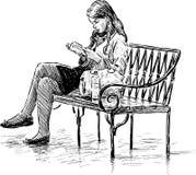 Leitura da menina em um banco de parque Imagens de Stock