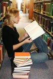 Leitura da menina na biblioteca Fotografia de Stock Royalty Free
