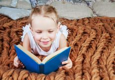 Leitura da menina na cama imagem de stock royalty free