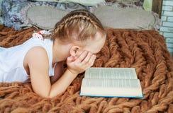 Leitura da menina na cama fotos de stock royalty free