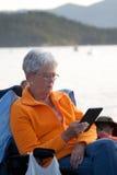 Leitura da mulher adulta eletronicamente Fotografia de Stock Royalty Free