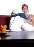 Leitura da mulher e chá bebendo Foto de Stock