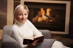 Leitura da mulher em casa fotografia de stock