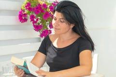 Leitura da mulher em uma loja do café Um momento de relaxamento fotografia de stock royalty free
