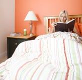 Leitura da mulher na cama foto de stock royalty free