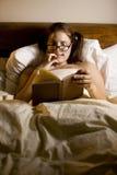 Leitura da mulher na cama Foto de Stock