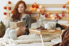 Leitura da mulher na cama imagem de stock