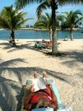 Leitura da mulher na praia fotografia de stock