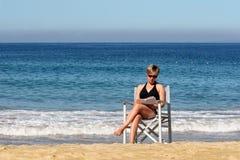 Leitura da mulher na praia fotos de stock royalty free