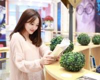 Leitura da mulher no mercado brilhantemente iluminado fotografia de stock royalty free