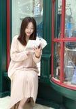 Leitura da mulher no mercado brilhantemente iluminado imagens de stock