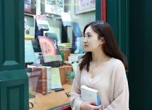 Leitura da mulher no mercado brilhantemente iluminado imagem de stock royalty free