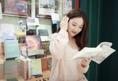 Leitura da mulher no mercado brilhantemente iluminado imagem de stock