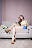 Leitura da mulher no sofá Fotos de Stock Royalty Free