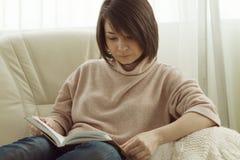 Leitura da mulher no sofá em casa foto de stock