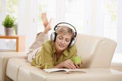 Leitura da mulher no sofá Fotos de Stock