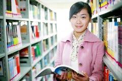Leitura da mulher nova na biblioteca Imagens de Stock Royalty Free