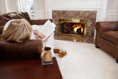 Leitura da mulher pelo incêndio Fotografia de Stock