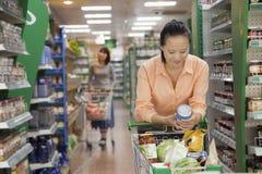 A leitura da mulher pode no supermercado, Pequim fotografia de stock royalty free