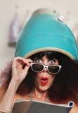 Leitura da mulher sob o secador de cabelo Fotografia de Stock