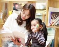 Leitura da prática da menina no mercado brilhantemente iluminado imagens de stock