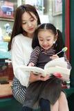 Leitura da prática da menina no mercado brilhantemente iluminado fotos de stock royalty free