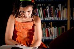 Leitura da rapariga em uma biblioteca Imagens de Stock