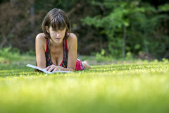 Leitura de relaxamento da jovem mulher na grama Imagens de Stock Royalty Free