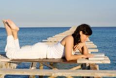 Leitura de relaxamento da mulher feliz fotos de stock
