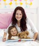 Leitura de sorriso da matriz e da filha na cama Fotos de Stock Royalty Free