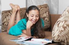 A leitura de sorriso da menina no sofá Imagens de Stock
