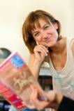 Leitura de sorriso da mulher com um amigo Fotos de Stock Royalty Free
