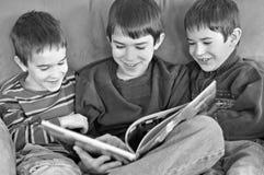 Leitura de três meninos Fotografia de Stock