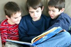 Leitura de três meninos Imagens de Stock