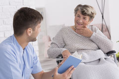 Leitura do cuidador para a senhora idosa fotografia de stock royalty free