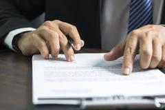 Leitura do homem de negócios ou do advogado e assinatura no papel do contrato em t Imagens de Stock